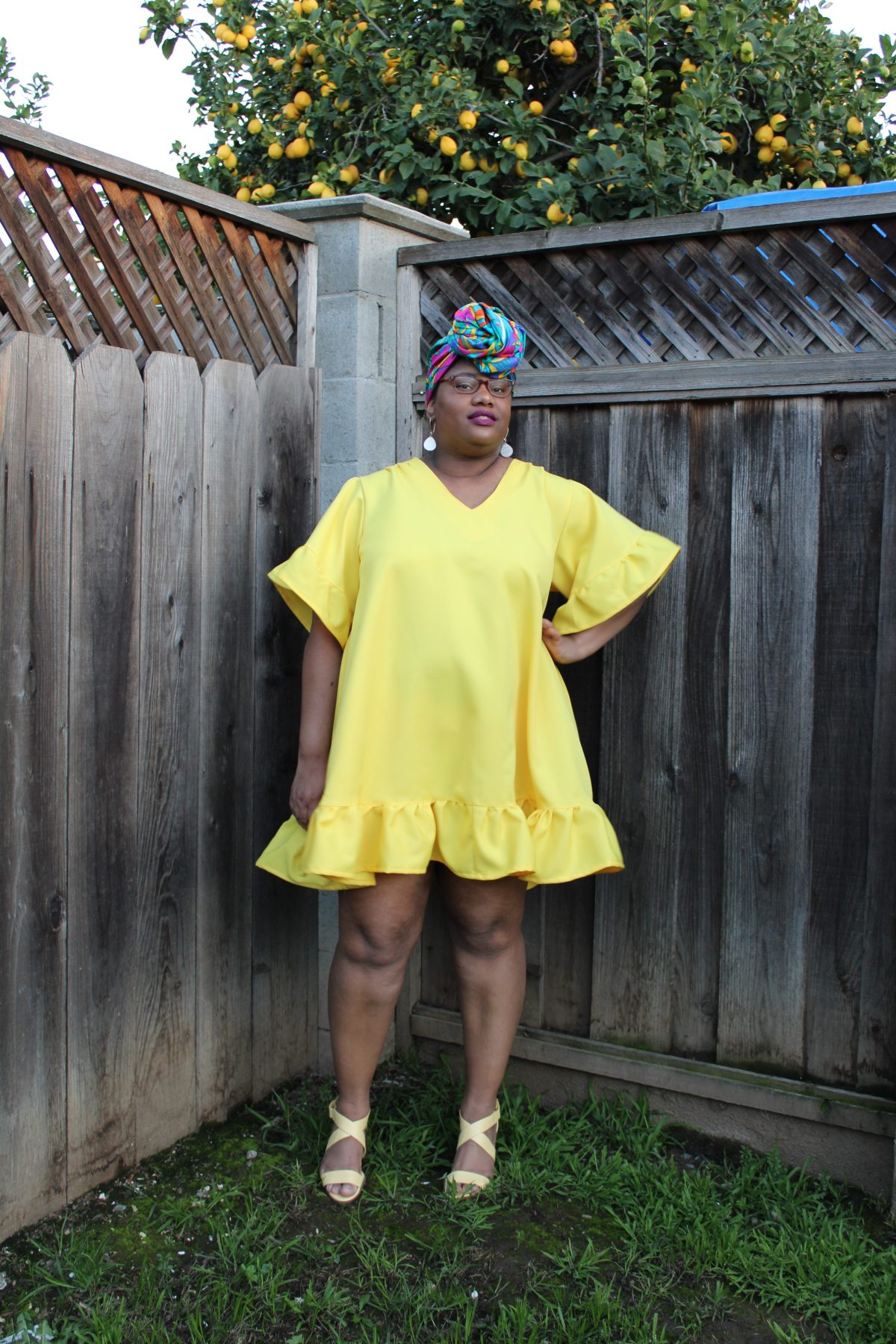 Image of a Black woman with a colorful head scarf. glasses, and dangling white earrings standing in front of a tall fence. Behind her, a lemon tree is heavy with lemons. She is wearing a bright mini A-line yellow dress and strappy yellow heels.