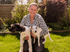 Abi is seen outside kneeling with her two dogs. She is wearing a grey shirt and black pants with white polka dots.