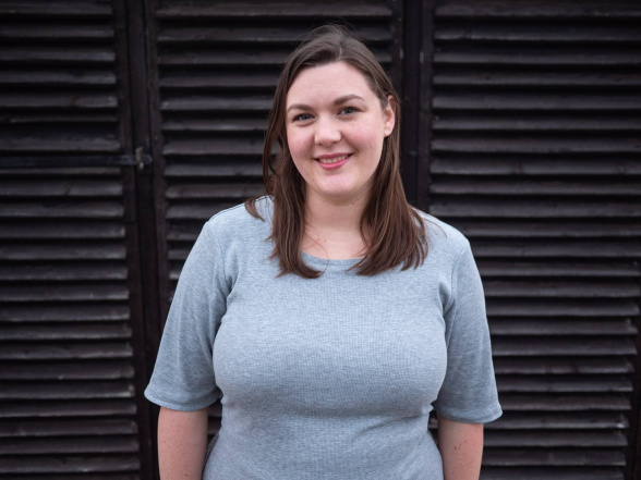 Brianna is standing in front of some black background and is wearing a blue-ish/grey-ish shirt.