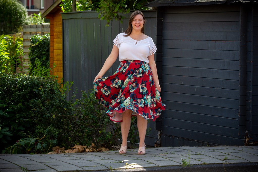 Brianna wears a floral skirt with a red background. It's a bit longer than knee length, and very full, and she is holding it out like she's swishing it. She's also wearing a white tee with a keyhole at the neckline and lace at the sleeves. She's standing outdoors on a paved path in a yard.
