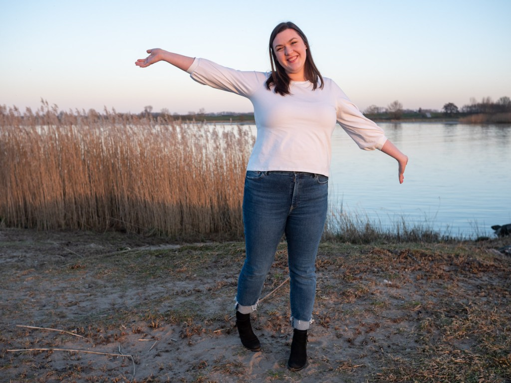 Brianna wears a white tee with three-quarter sleeves that are slightly gathered for a puff effect. She's standing by the lake, with her arms spread wide and a grin on her face.