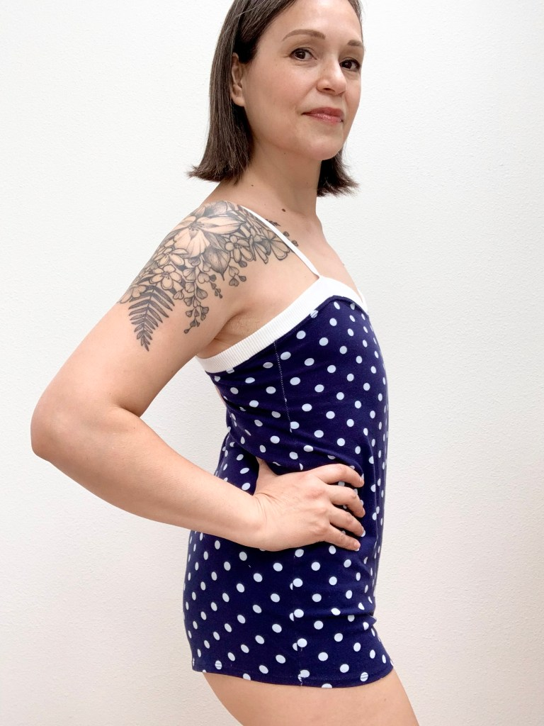 Woman without breasts standing in front of a background with hands on her hips wearing a dark blue and white polka dot romper