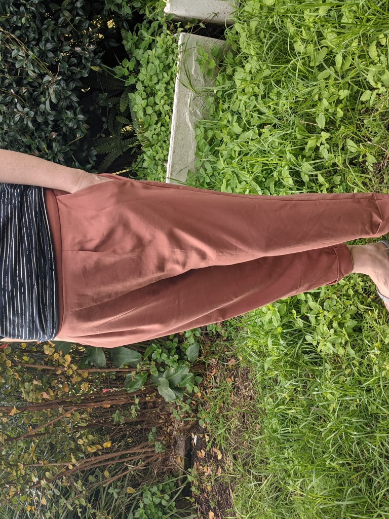 A picture of a woman from the neck down standing in an overgrown garden wearing a blue and white irregular striped t-shirt and a pair of salmon coloured pants.  She has her hands in her pockets.