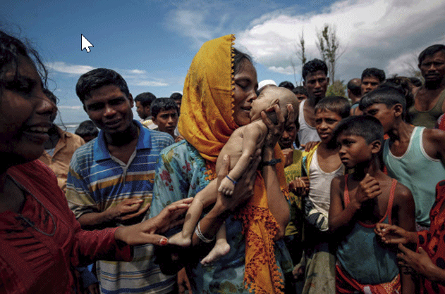 Hamida, a Rohingya refugee woman, weeps as she holds her 40-day-old son after he died as their boat capsized before arriving on shore in Shah Porir Dwip, Teknaf, Bangladesh (Part of Reuters series that won Pulitzer for feature photography).