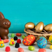 Easter conceptual image on blue wooden background with copyspace chocolate Easter rabbit, candy, sweets, baby chicken and Easter eggs in basket