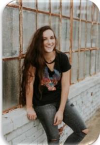 teen girl sitting on outside ledge
