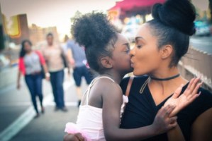 woman kissing child on cheek