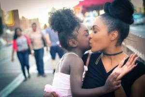 woman kissing child on cheek