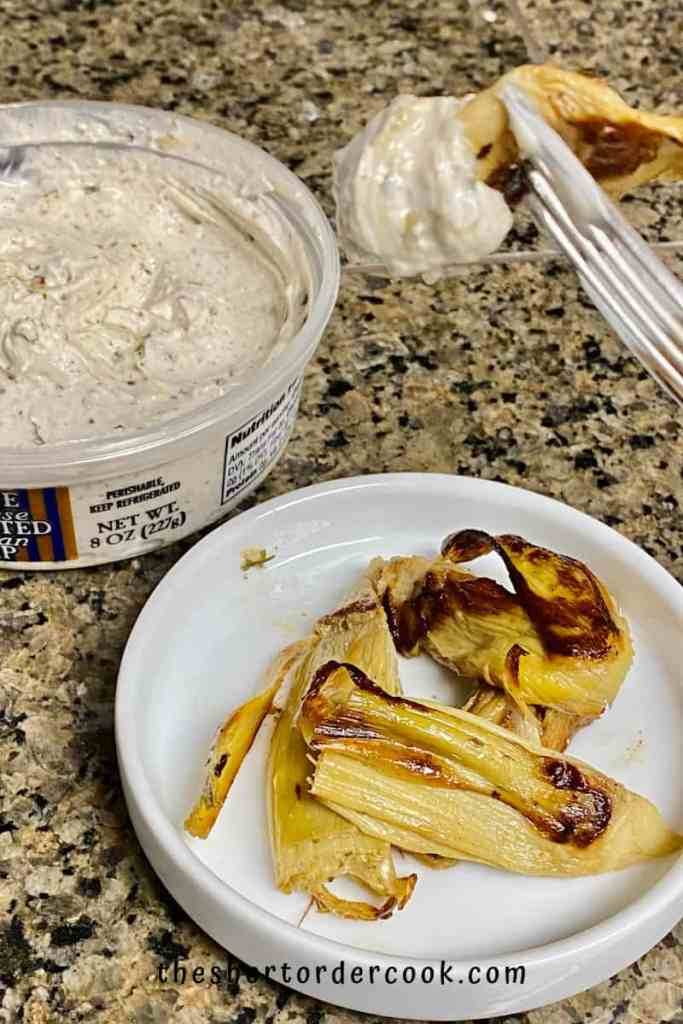 Crispy Baked Marinated Artichoke Hearts plated and a fork used to dip one into a cheese dip