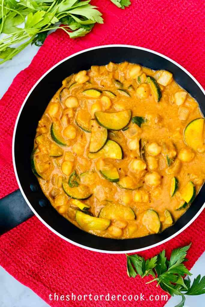 Zucchini, Chickpea, & Potato Curry ready in the pan overhead overhead with parsley on the side