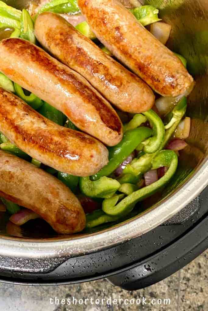 Instant Pot Italian Sausage & Peppers with sausages layered on top of the peppers and onions