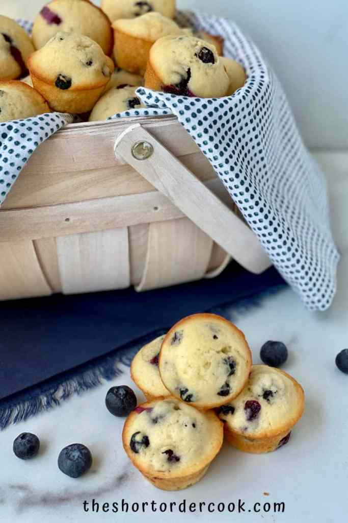 Old-Fashioned Mini Blueberry Muffins basket full and a four stacked on the side with blueberries and blue cloth napkin
