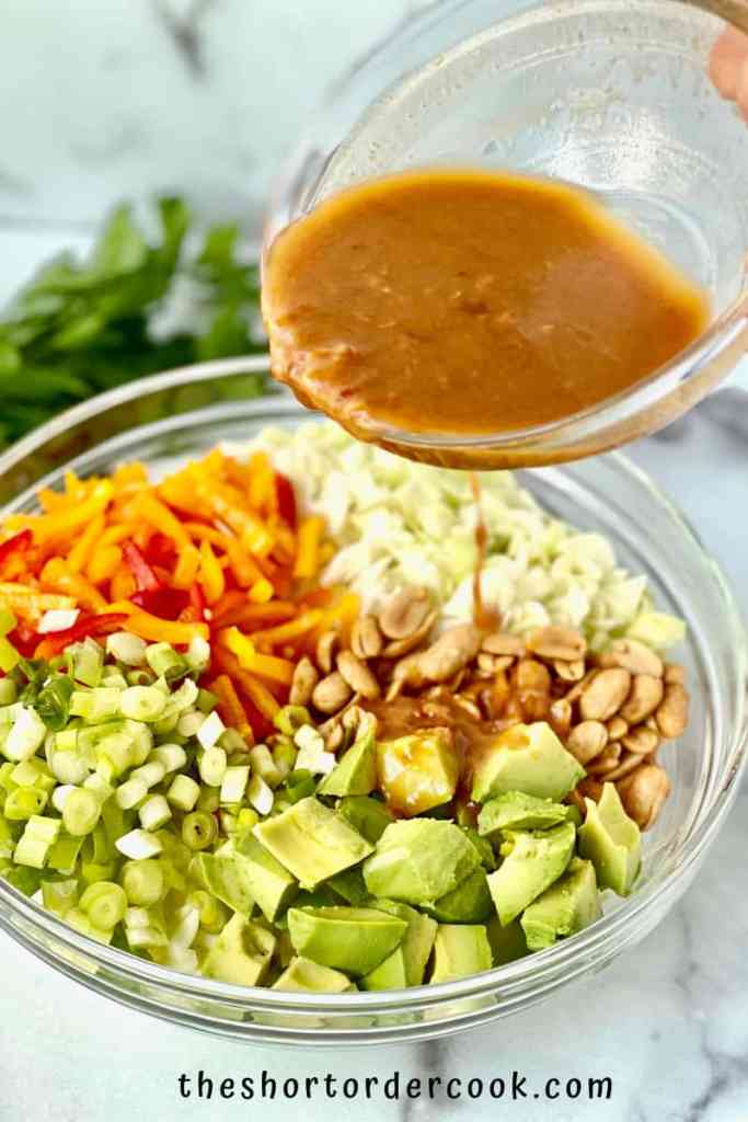 Asian Avocado Peanut Coleslaw pour the dressing on the salad ingredients