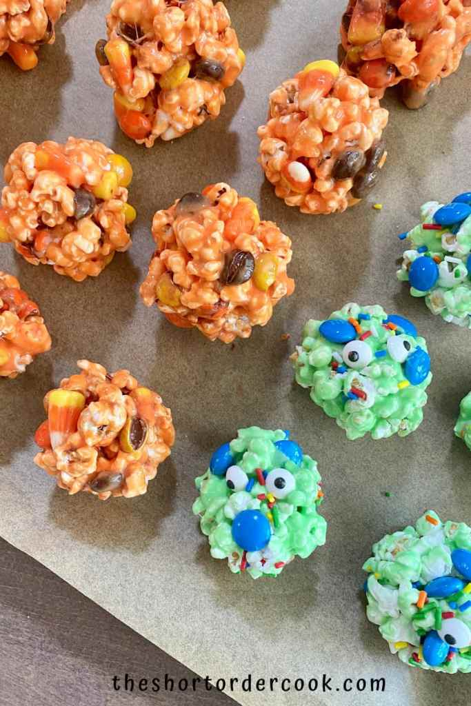Halloween Popcorn Balls about a dozen popcorn balls lined up on a parchment paper lined baking sheet