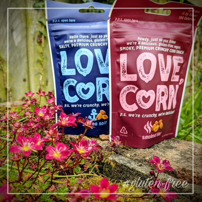 Two bags of Love,Corn gluten free snacks one is sea salt flavour and one is smoked barbecue flavour sitting on a wall with flowers
