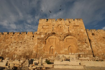 Birds fly over the golden gate walls as the sunrises over the old city of jerusalem