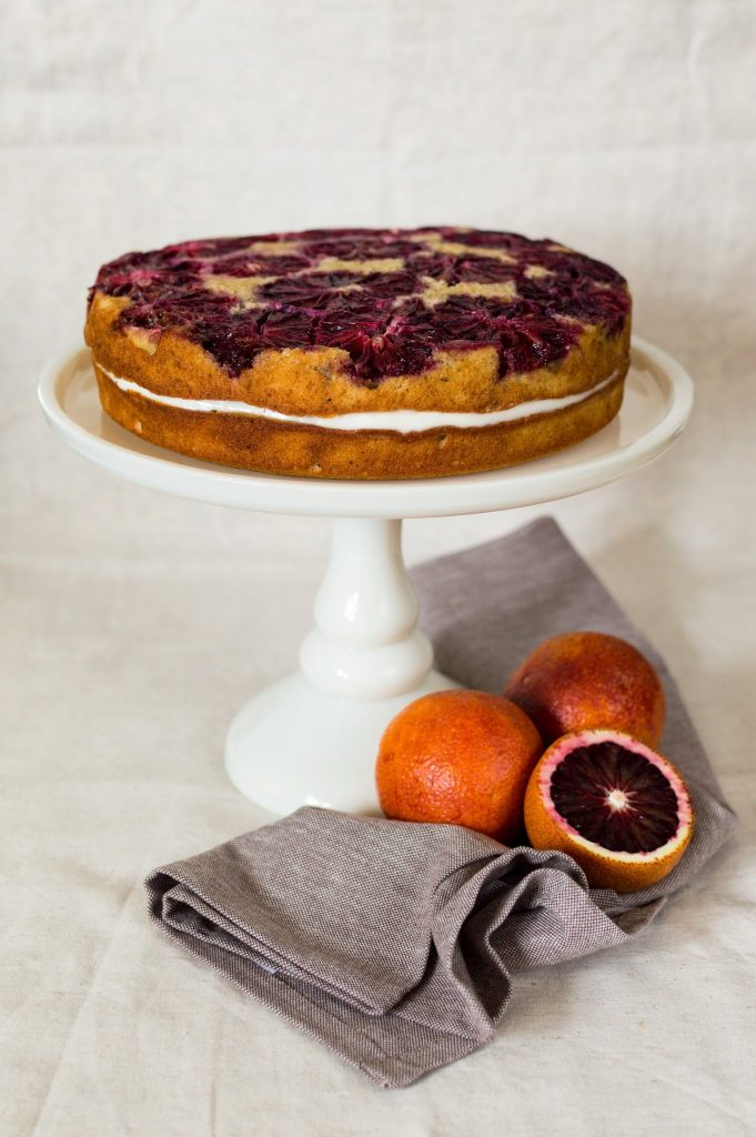 blood orange spice cake on a white cake stand