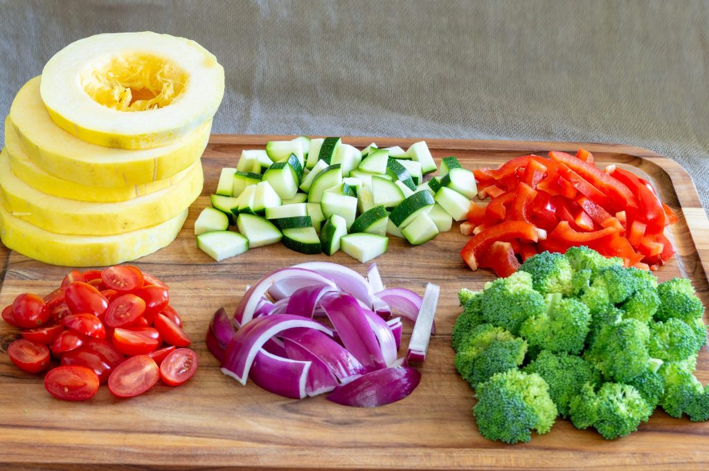 spaghetti squash, broccoli, peppers, onion, tomatoes chopped on a cutting board
