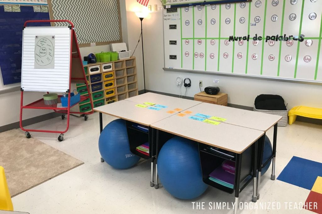 4 student desks sitting in a classroom with yoga balls as the chairs. Word wall and math center storage in the background.