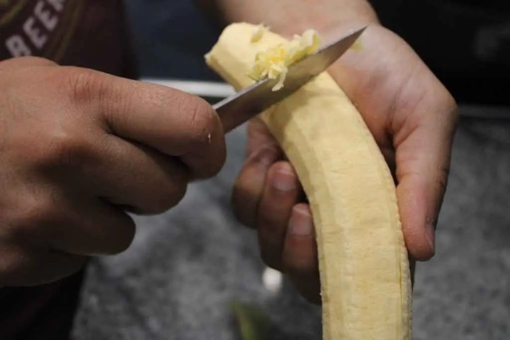 This is how you shave off any excess pieces of the plantain peel using a knife.