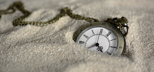 pocket watch buried in sand