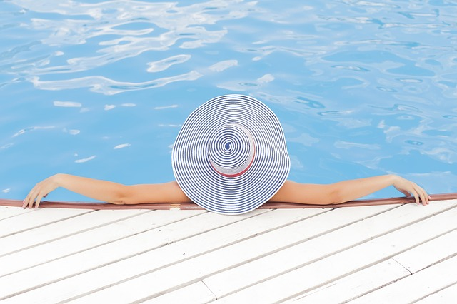 person with big hat relaxing in pool