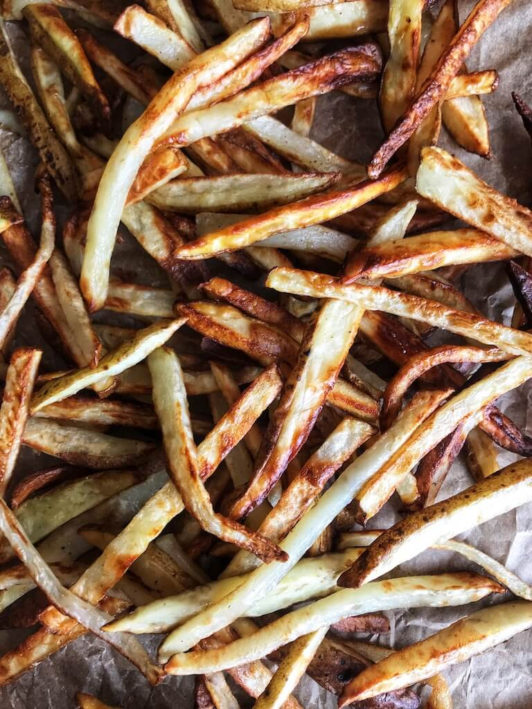 Air Fryer Crispy French Fries spread out across parchment paper