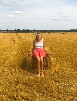 young female sat on bale of straw