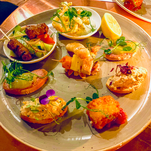 Plate of canapes including pork belly, duck liver, lamb koftas, deep fried brie and salt and pepper squid