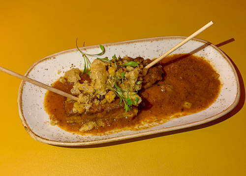 Two skewers of roast pork belly topped with a pineapple salsa and chicharrónes, served with a tangy tamarind glaze.