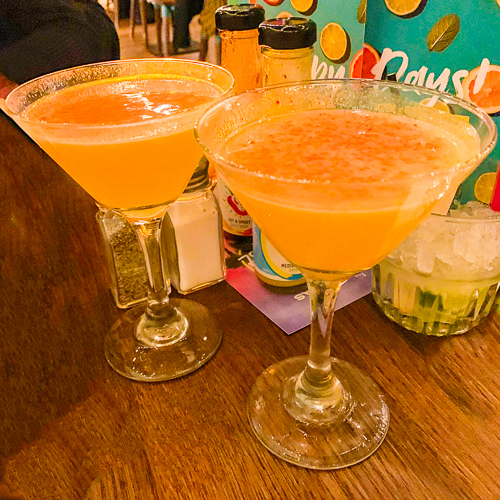 Two martini glasses with a passion fruit cocktail