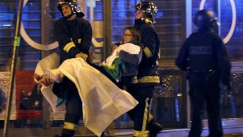 Fire brigade members aided a wounded woman near the Bataclan concert hall, one of the sites of the explosions. Photo courtesy of Christian Hartmann, Reuters