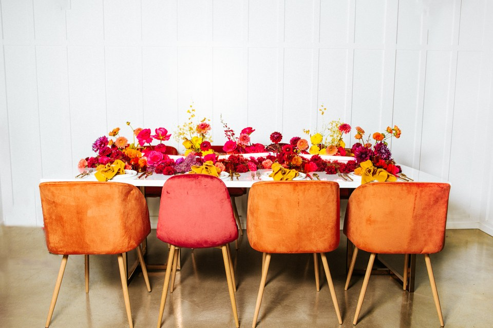 Velvet chairs and colorful flowers at wedding table