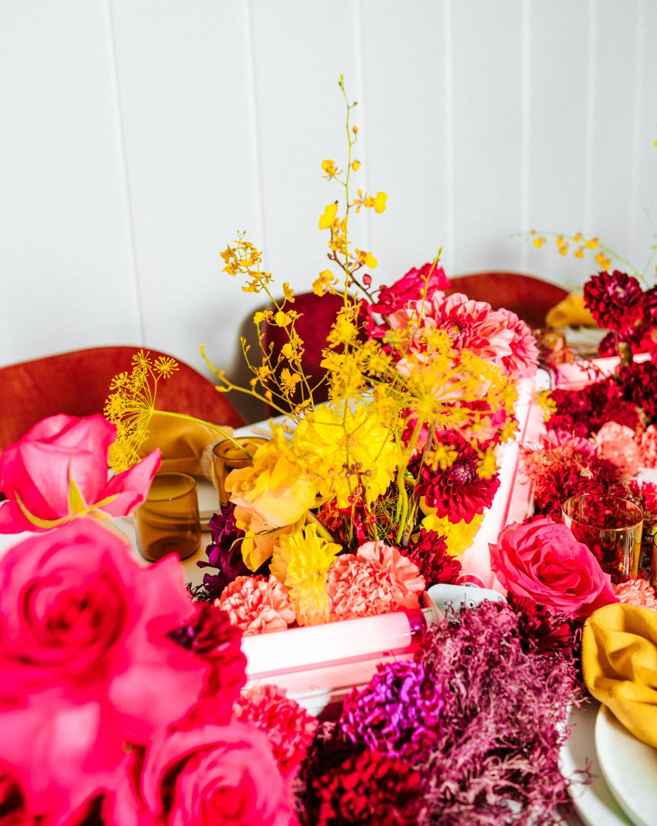 Bright red, pink, and yellow wedding flower centerpiece