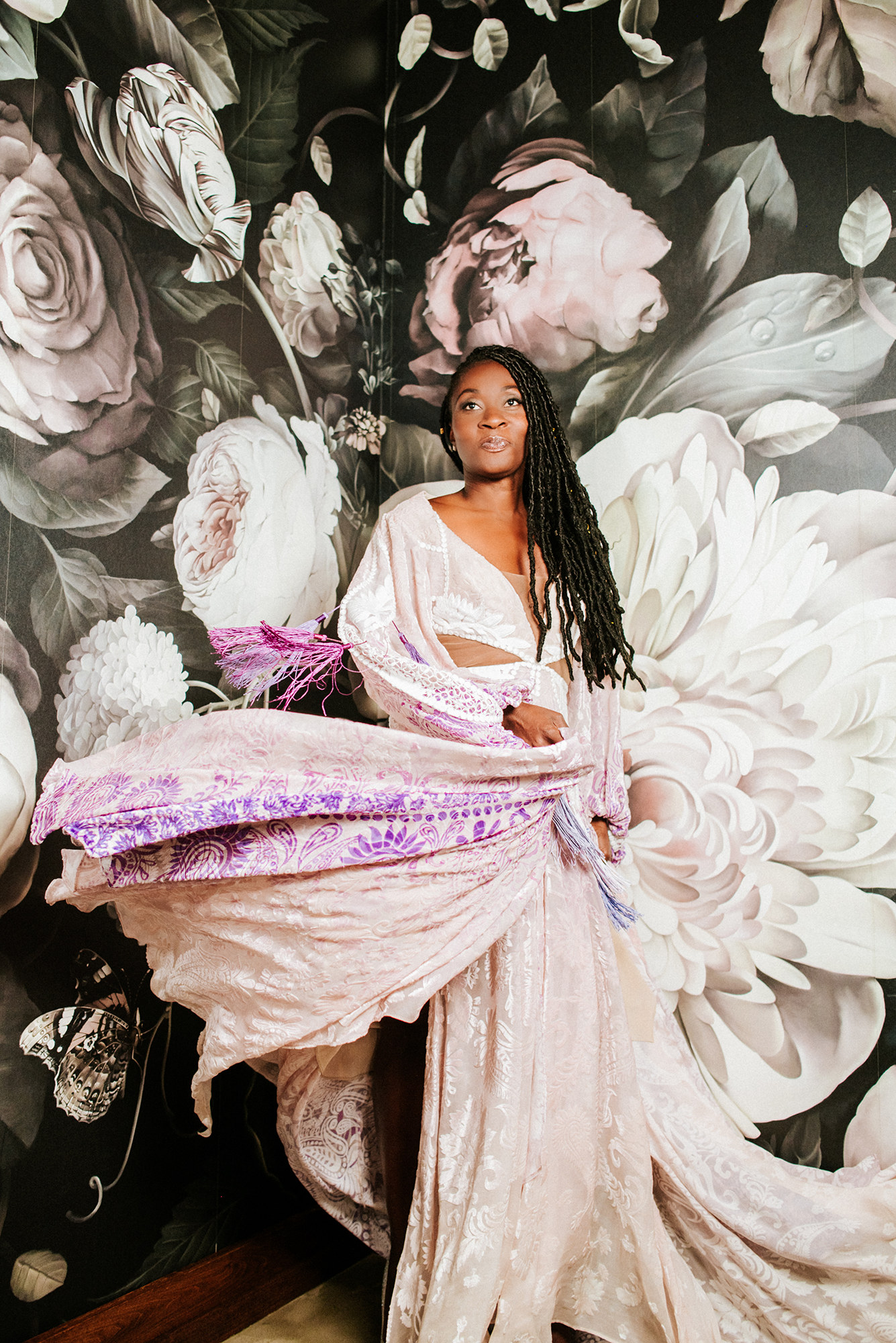 Black bride twirling in a white and purple boho gown