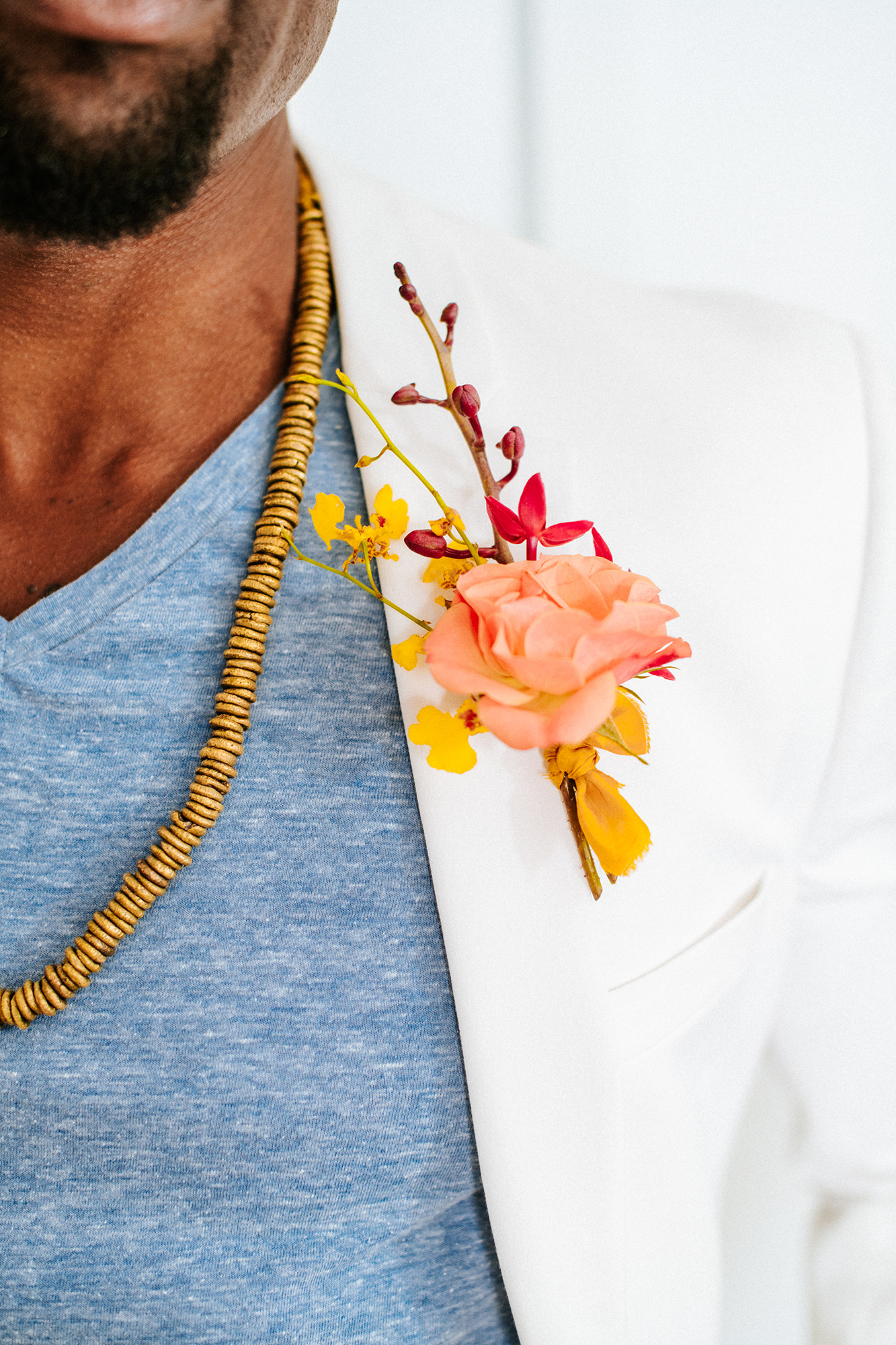 Black groom in white tux with colorful boutonniere