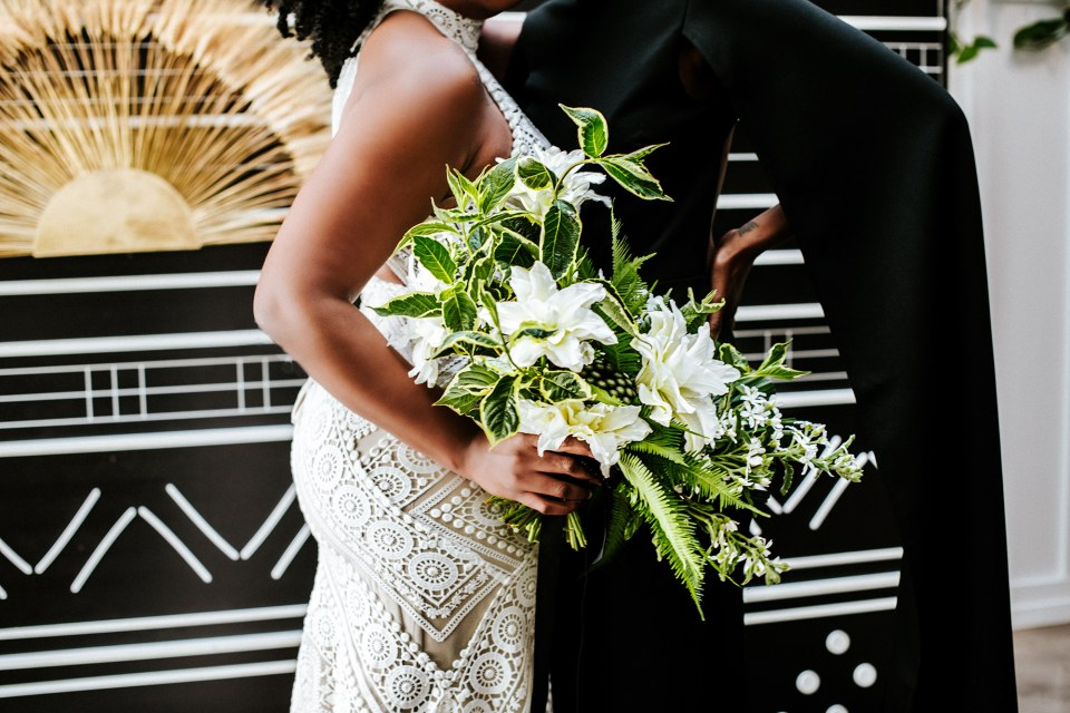 Black gay couple with bridal bouquet at their modern black and white wedding