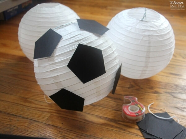 """These """"floating"""" soccer paper lanterns are the perfect addition to a sports themed kids birthday party or bedroom decor! Easy & thrifty DIY! (free pattern)"""