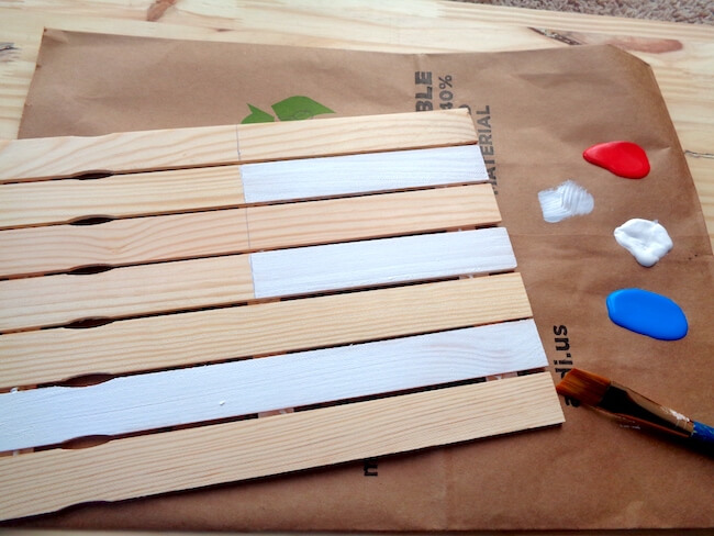 painting white stripes on a wooden American flag