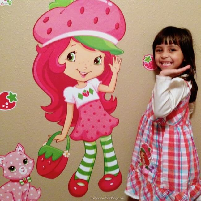 Three year old girl posing with Strawberry Shortcake