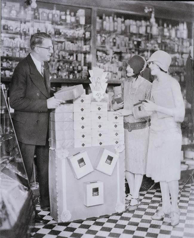Women line up at store display of Modess tampons circa 1920s