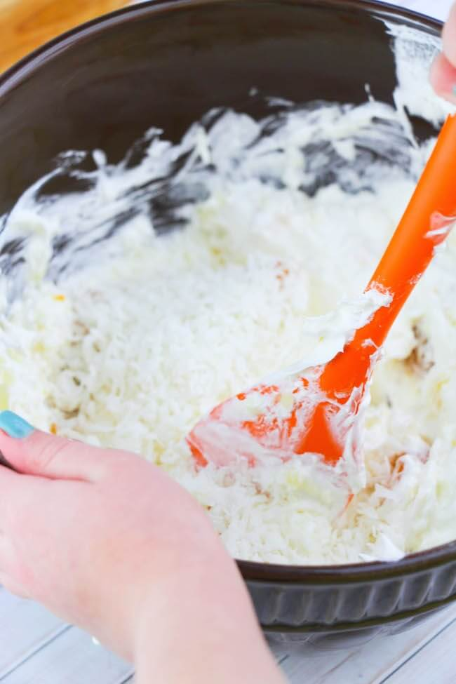 Stirring sour cream and Cool Whip for Ambrosia Salad