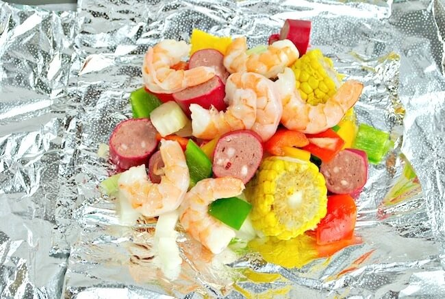 Chopped veggies, shrimp, and sausage on foil