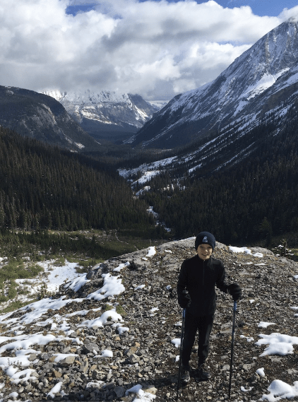 Author's son, an eight-year-old boy, stands on a snow-dusted outcropping overlooking Peter Lougheed Provincial Park. He is dressed in long pants and a long-sleeve shirt, with gloves, a winter toque, and hiking poles.