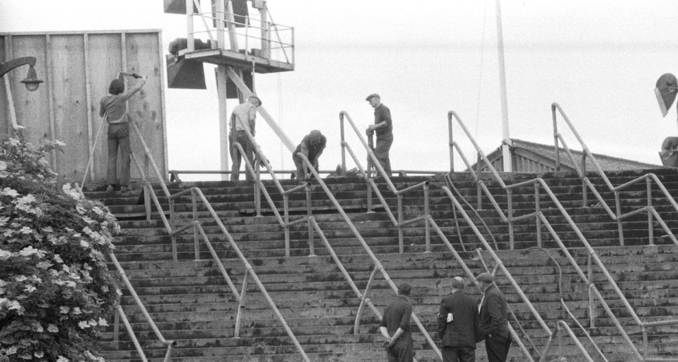 A black and white photo shows a stairwell at Ibrox Stadium in 1971 in which workers clear away debris.