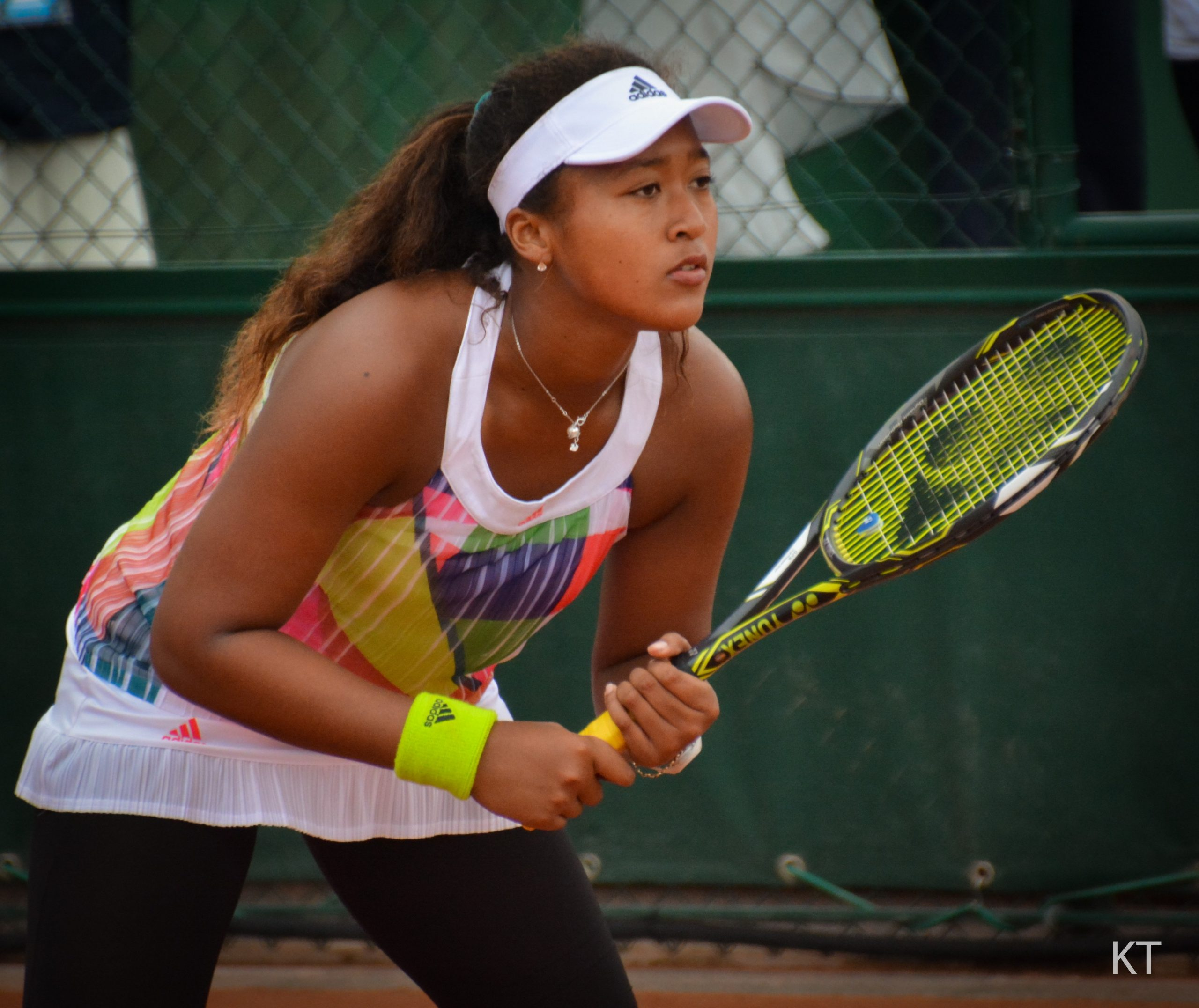 Naomi Osaka, wearing a white visor and colorful shirt, stands reads to hit a tennis ball