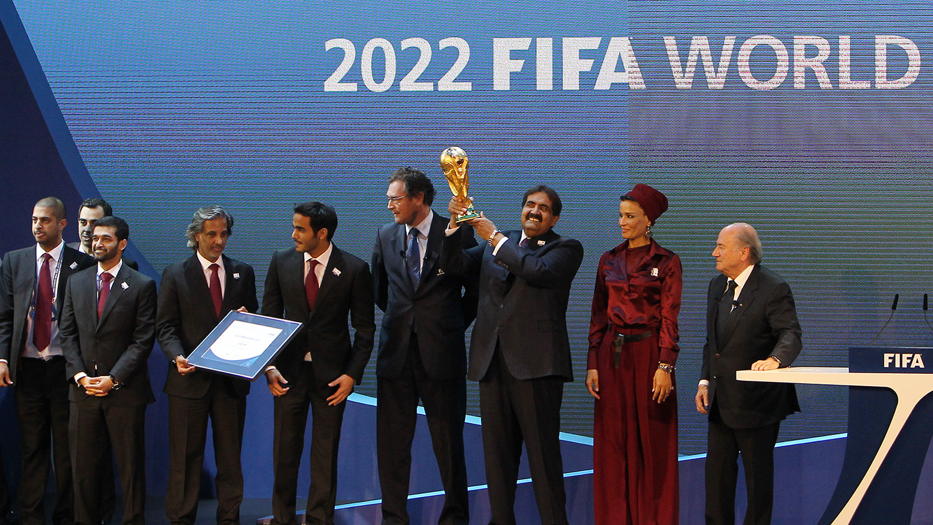 A group of Qatari soccer officials, one holding the World Cup trophy, stand next to FIFA President Sepp Blatter after being named the host nation for the 2022 World Cup.