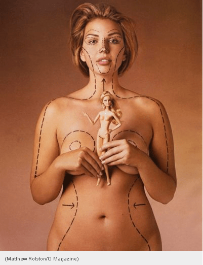 "A white woman's naked body is shown from the hips up, her arms are held in front of her breasts.  She is holding a Barbie doll.  On her body and face are ""surgical lines"" indicating where she deviates from the Barbie ideal."
