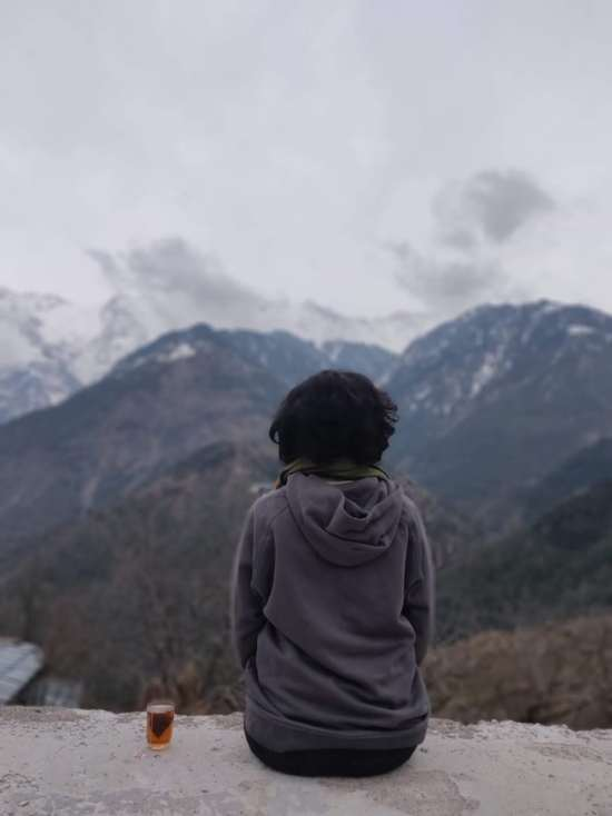 women looking at himalayas with a cup of tea