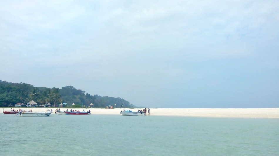 beach with few paddle boats on one side and a strip of white sand on horizon
